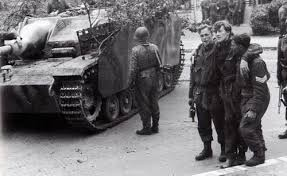 "The aftermath of Arnhem. A StuG III of the 9. SS Panzer Division Hohenstaufen and captured British paratroopers. SS soldiers from both Hohenstaufen and Frundsberg were involved in the battle, and their treatment of the prisoners afterwards was exemplary. Lieutenant-Colonel John Frost, one of the British officers who took part and was captured, describes the SS thus: ""We had all heard of them shooting their prisoners or herding them into burning buildings, but these men were kind, chivalrous and even comforting."" After Arnhem, Hohenstaufen was pulled back to Germany to prepare to take part in the Ardennes Offensive. It then took part in the abortive attempt to retake Budapest."